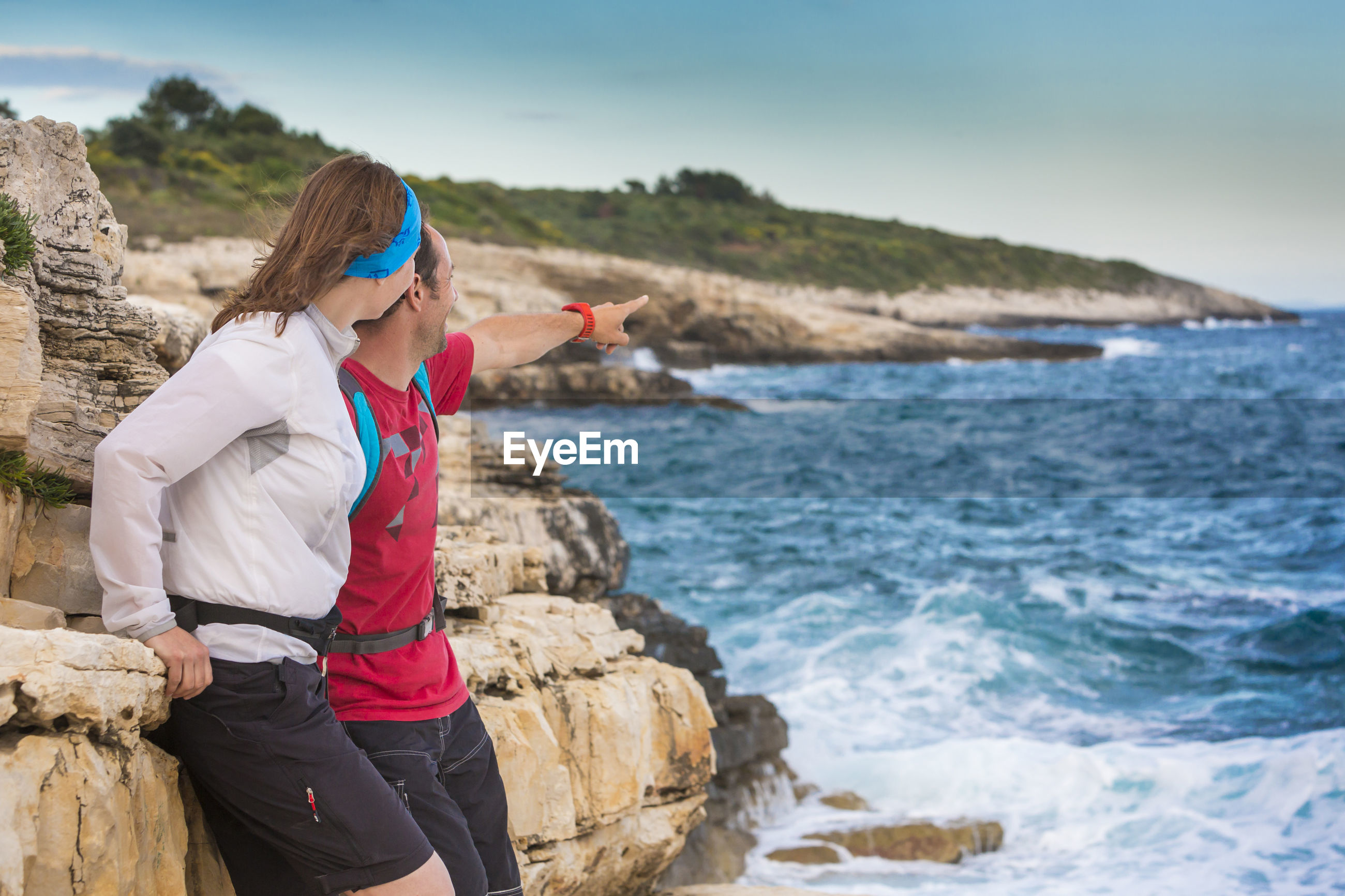Man pointing by woman standing on rocky shore