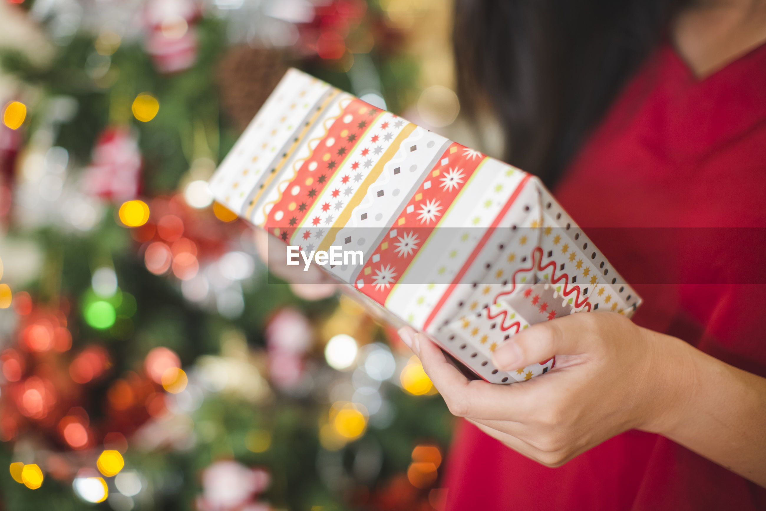 Close-up of woman holding christmas present while standing against tree