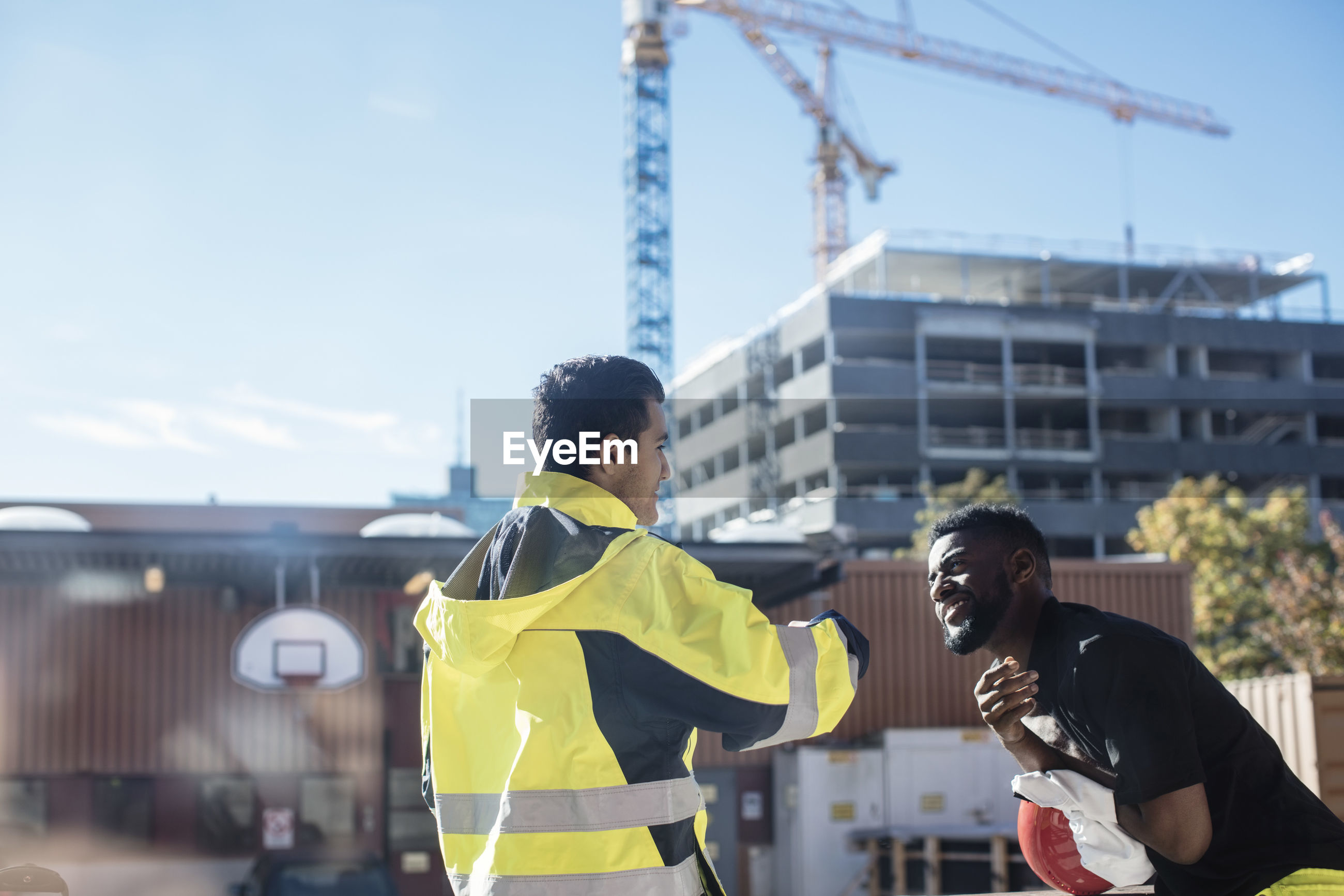 PEOPLE STANDING ON CONSTRUCTION SITE AGAINST SKY