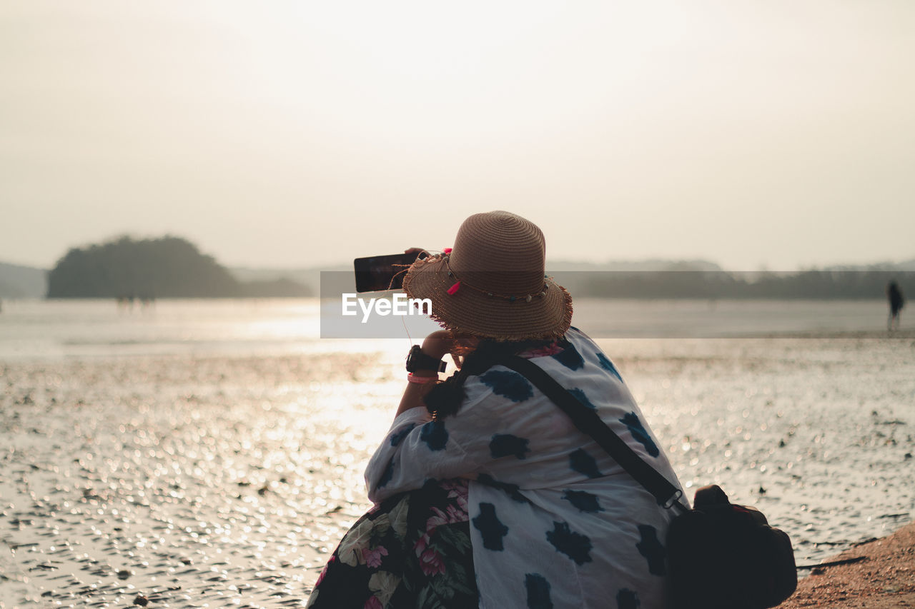 Rear view of woman crouching and photographing from smart phone against sky