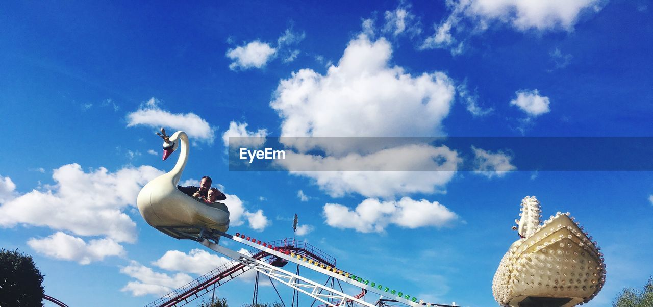 cloud - sky, sky, low angle view, nature, day, blue, representation, no people, bird, flying, outdoors, arts culture and entertainment, architecture, amusement park, art and craft, animal wildlife, animal, built structure, animal representation, animal themes