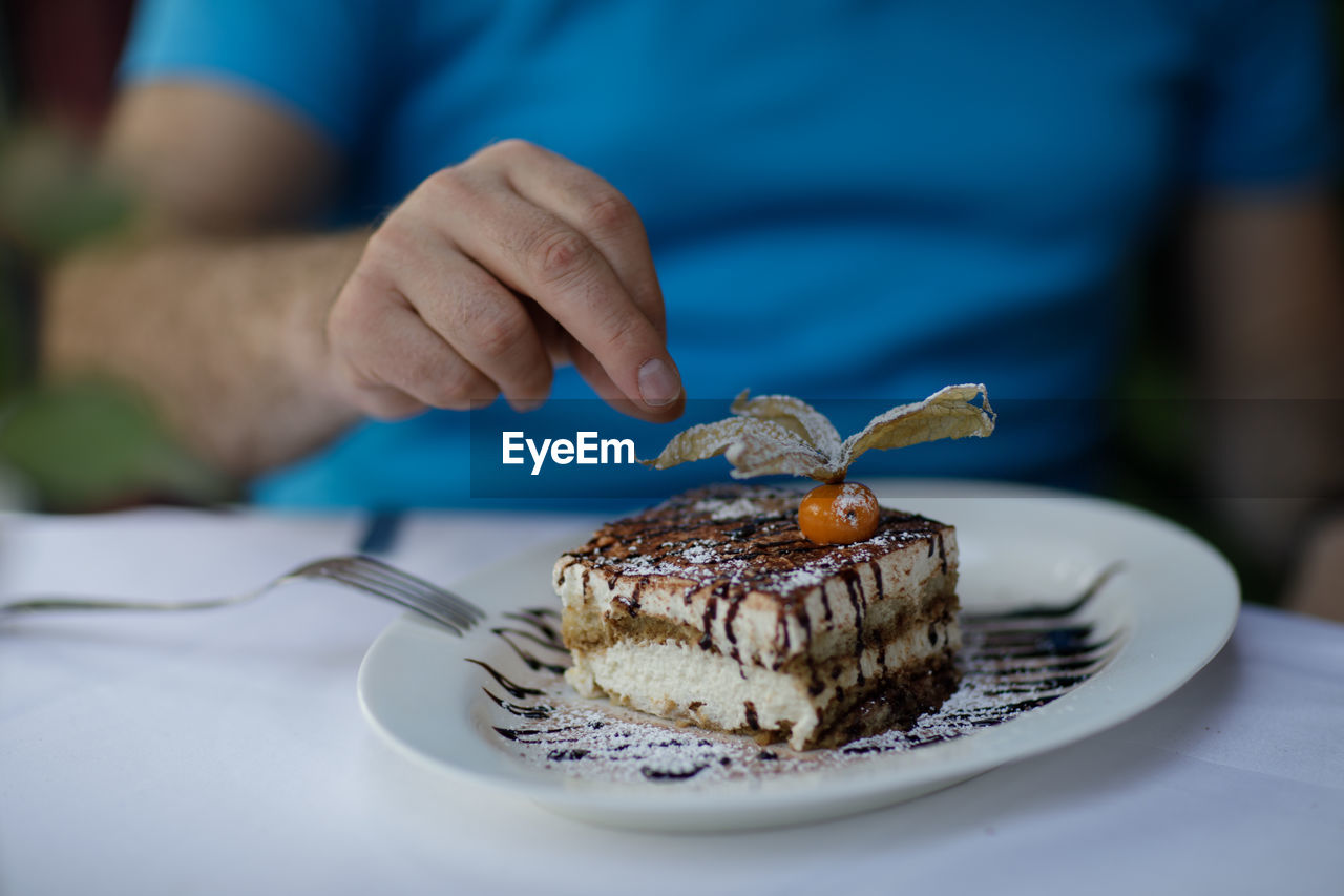 Midsection Of Men Having Dessert At Table