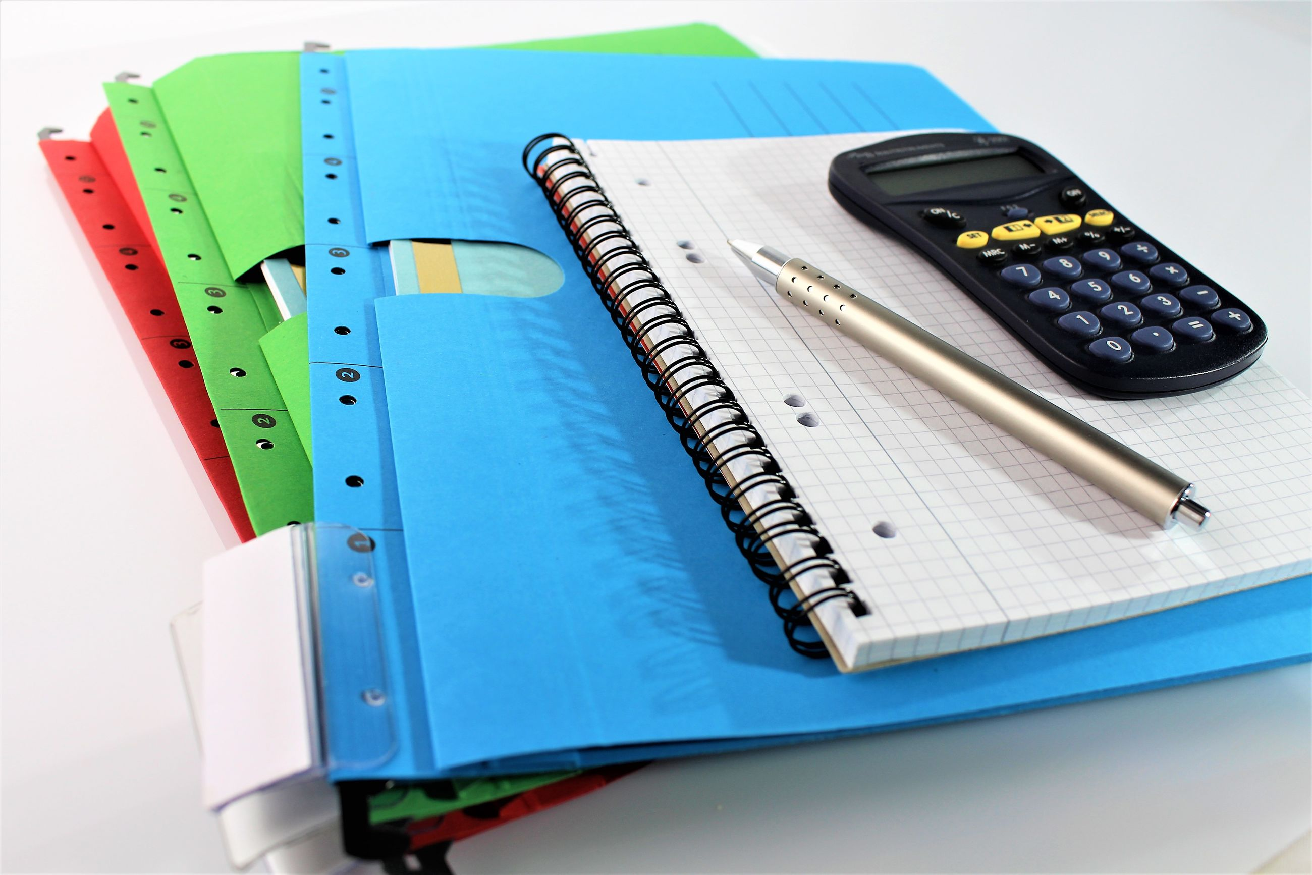 Close-up of calculator with books and pen over white background
