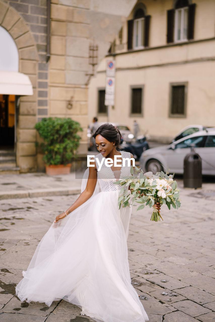 Full length of bride holding flower bouquet on street