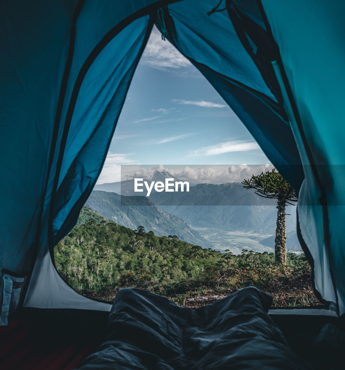 Low Section Of Person Relaxing In Tent Against Mountains