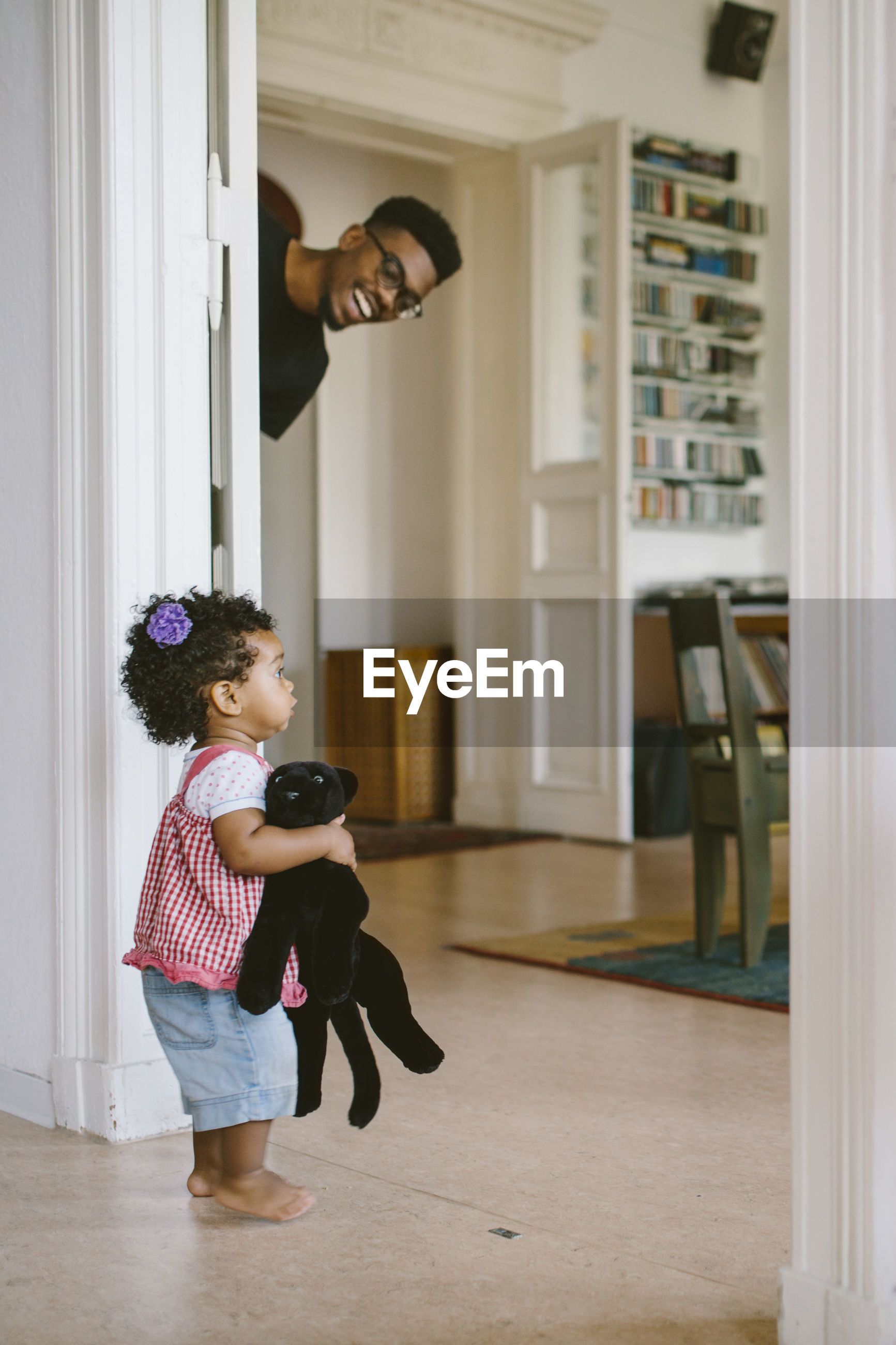 Happy father peeking at daughter holding stuffed toy in house