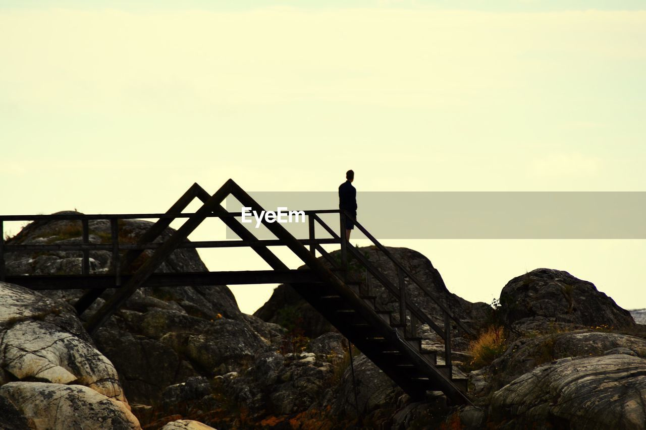 rock - object, one person, full length, real people, standing, silhouette, outdoors, men, leisure activity, nature, scenics, day, sky, lifestyles, adventure, beauty in nature, climbing, clear sky, one man only, people