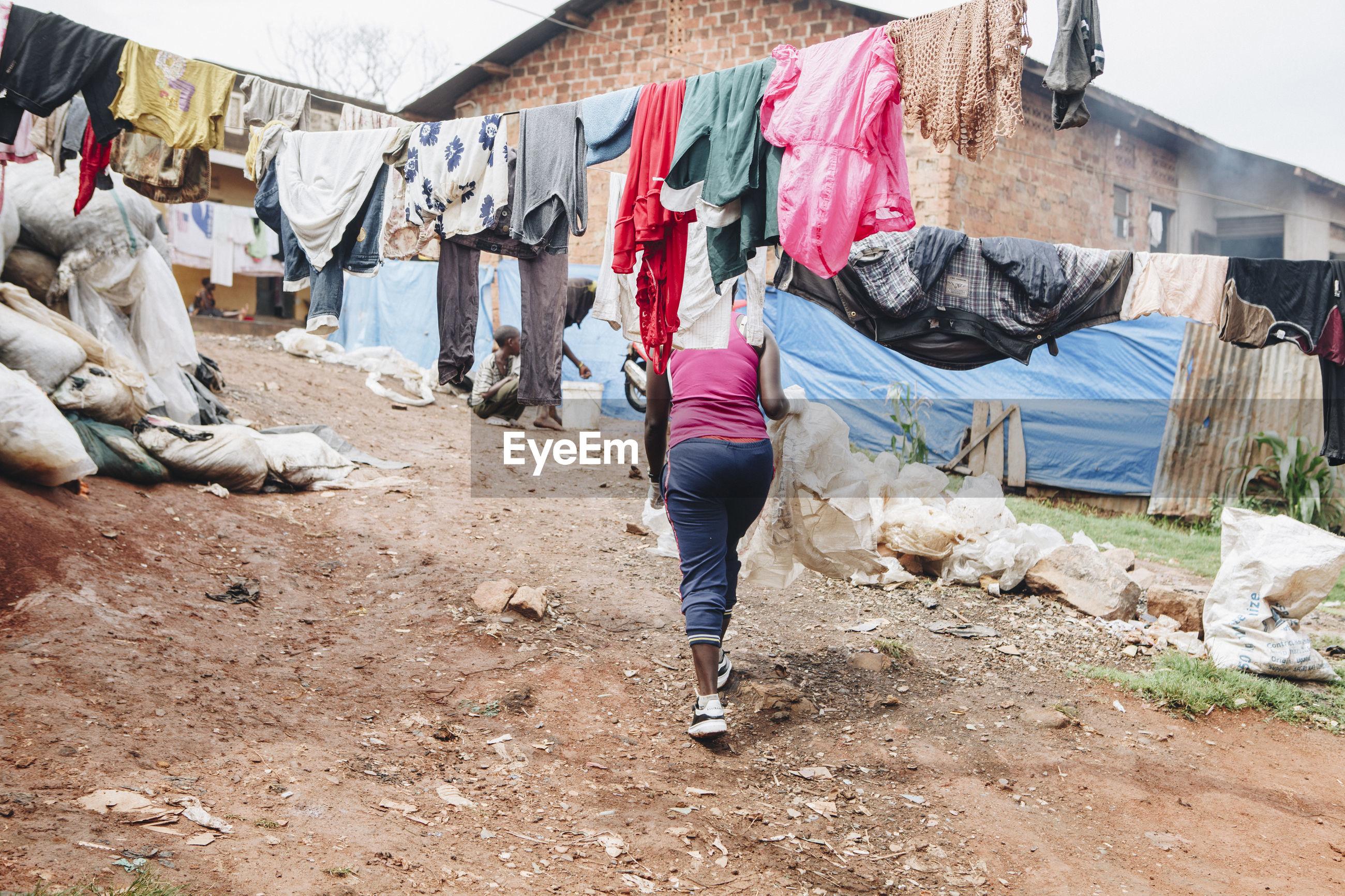 Low section of woman walking on field in slum