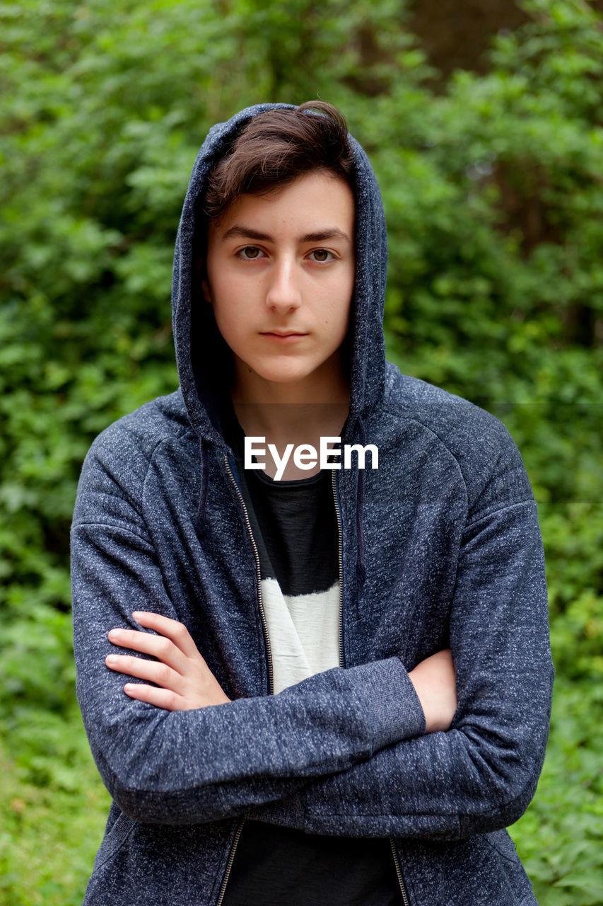 Portrait of boy wearing hoodie standing against trees