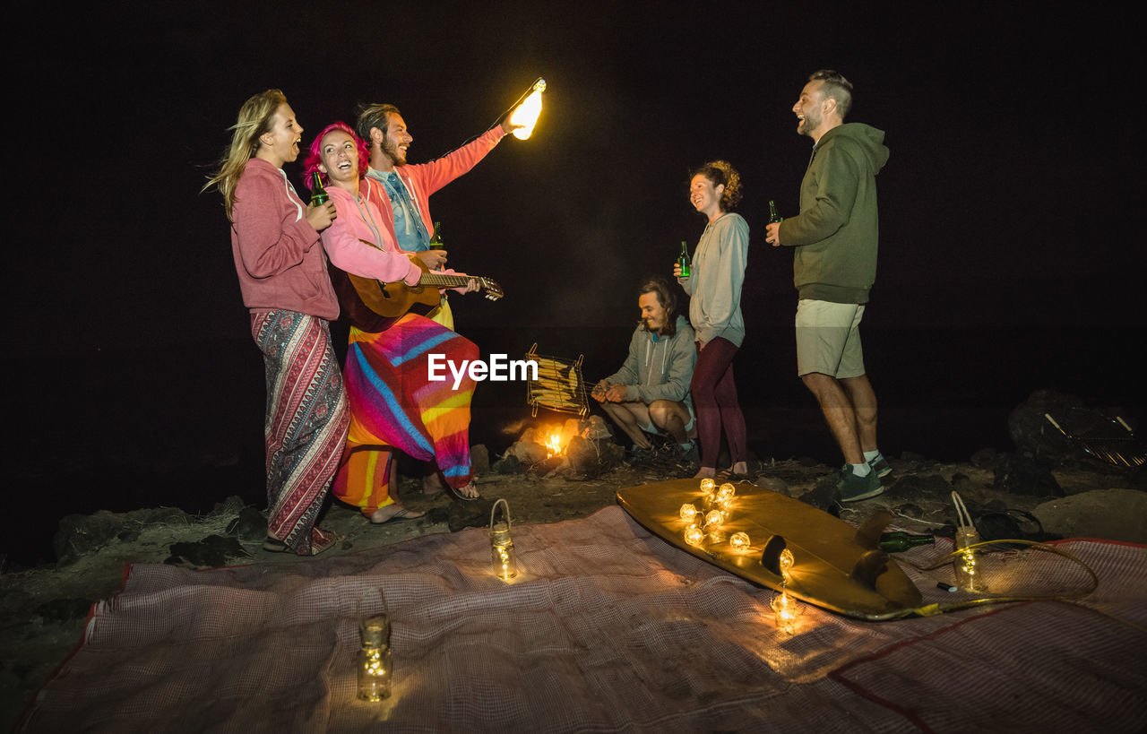 Friends standing by illuminated lighting equipment while camping at night