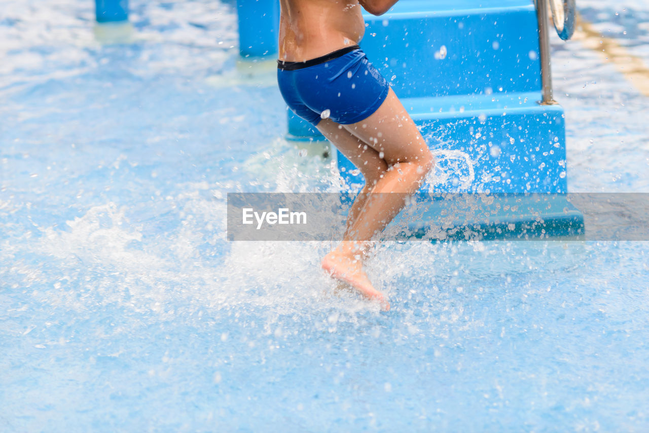 Low Section Of Boy Running In Water By Steps
