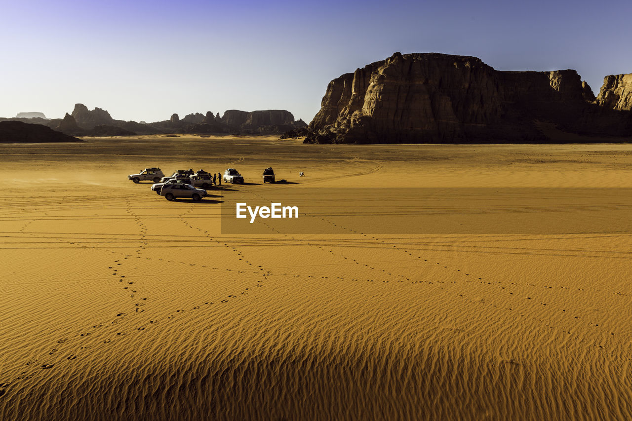 sky, sand, land, scenics - nature, mode of transportation, transportation, beauty in nature, desert, nature, clear sky, rock, tranquil scene, day, tranquility, land vehicle, rock formation, rock - object, landscape, environment, solid, arid climate, climate, outdoors
