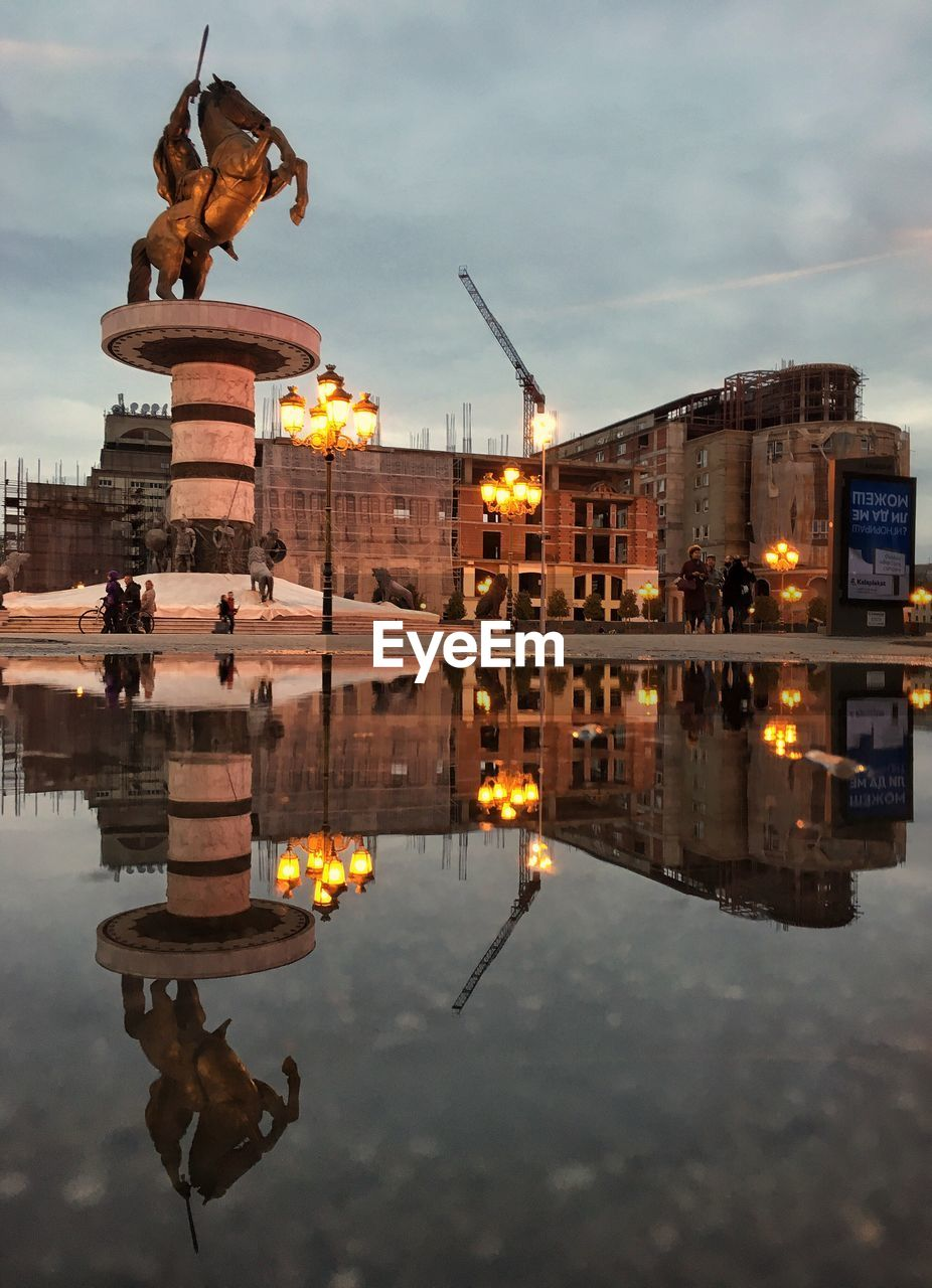 reflection, architecture, built structure, building exterior, water, history, waterfront, travel destinations, reflecting pool, sky, outdoors, illuminated, cloud - sky, travel, statue, no people, place of worship, sculpture, city, day, puddle, animal themes