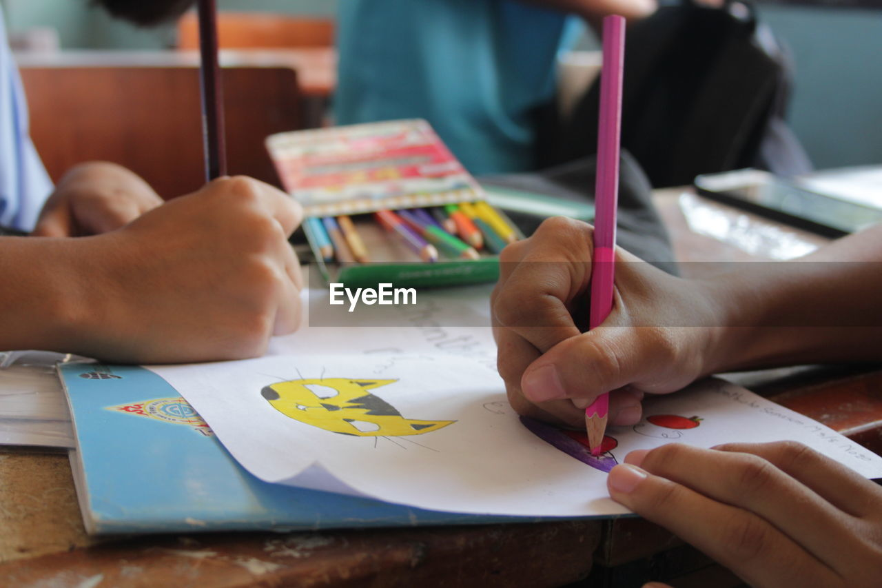 Close-Up Of Children Drawing On Paper