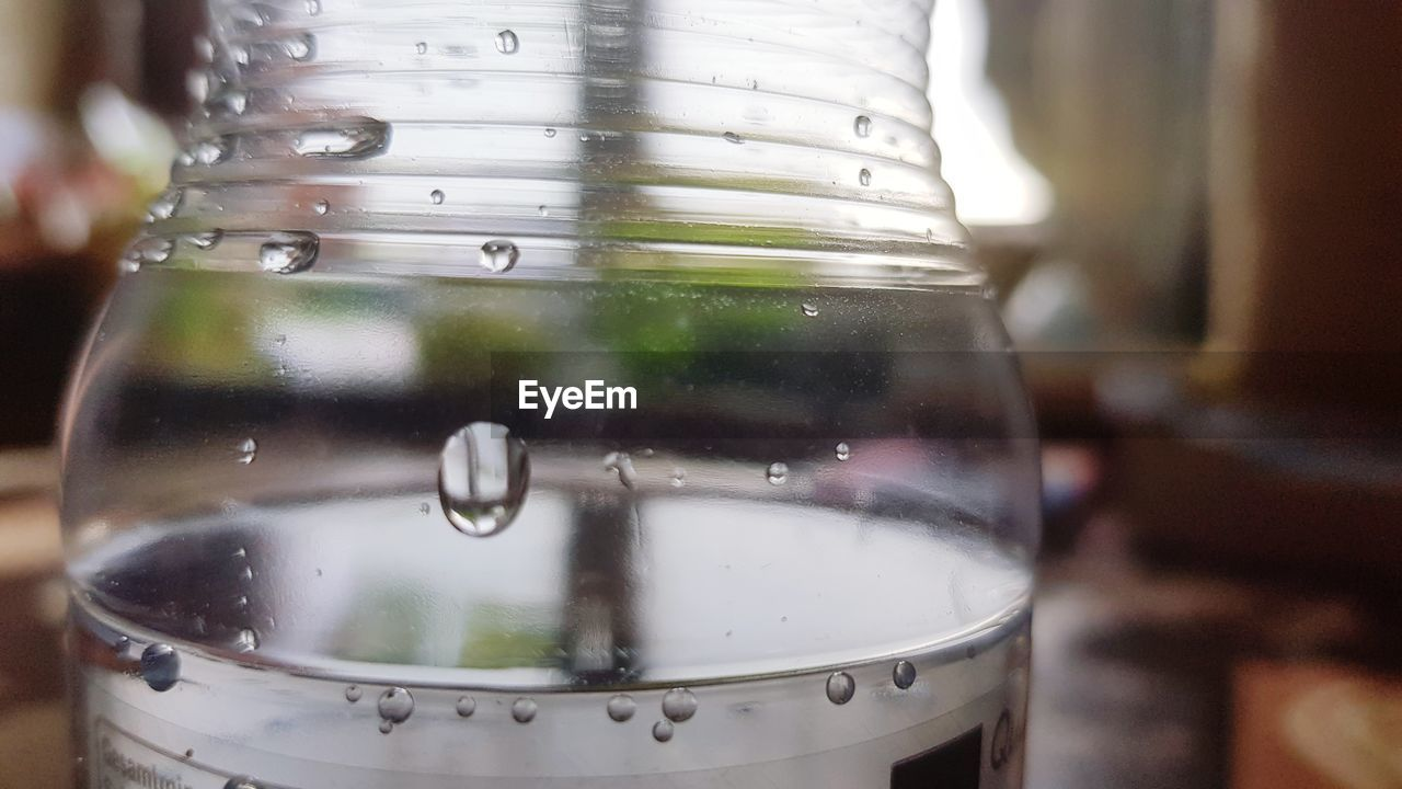 close-up, focus on foreground, transparent, container, glass - material, water, no people, food and drink, indoors, refreshment, drink, glass, still life, household equipment, wet, bottle, metal, drinking water, reflection
