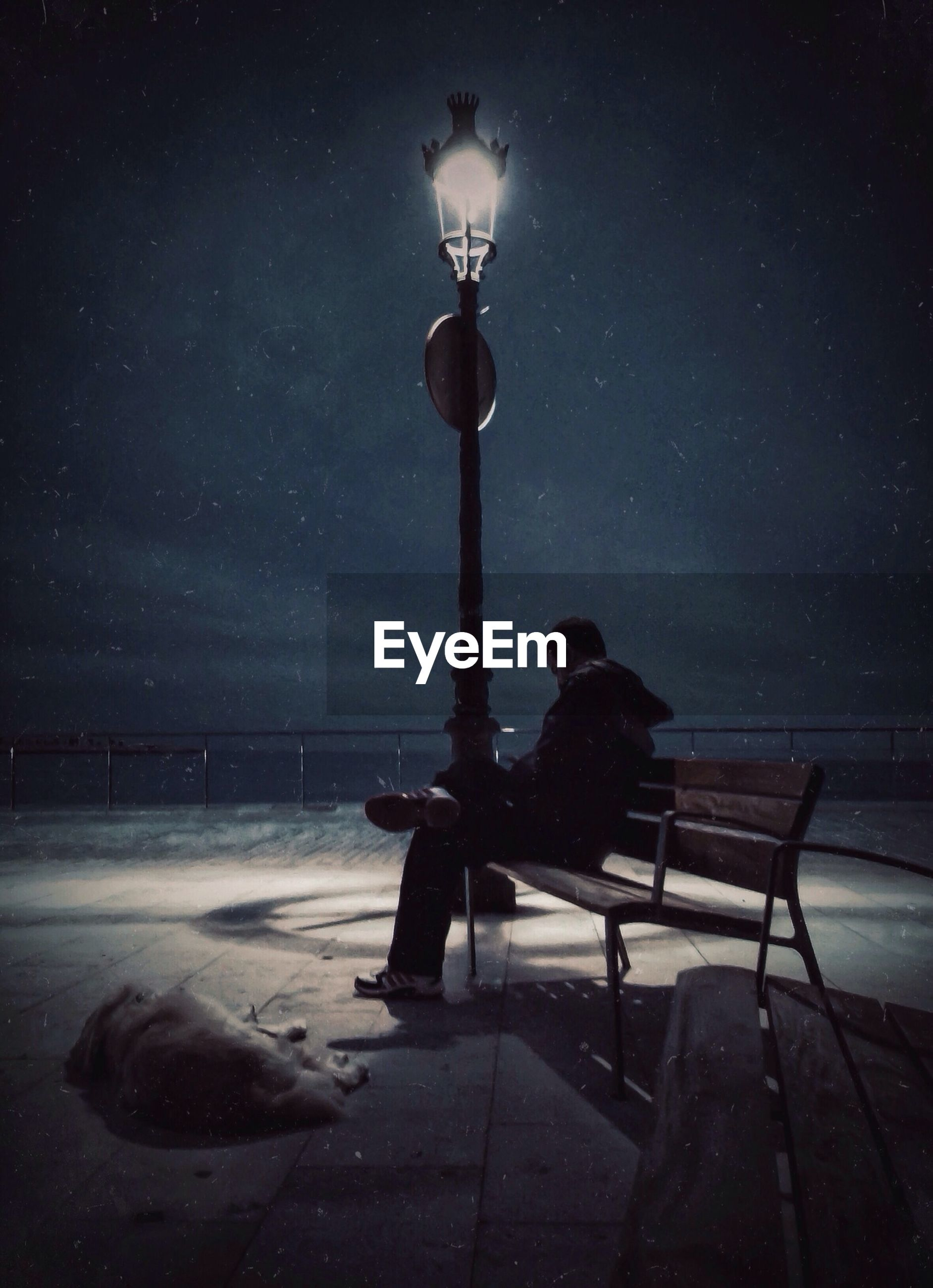 Man sitting on park bench at night