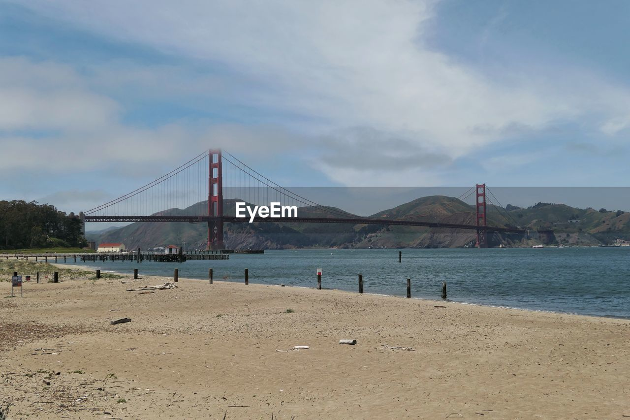 water, sky, beach, built structure, cloud - sky, bridge - man made structure, bridge, architecture, sea, connection, mountain, land, nature, day, sand, engineering, incidental people, transportation, travel destinations, bay, outdoors