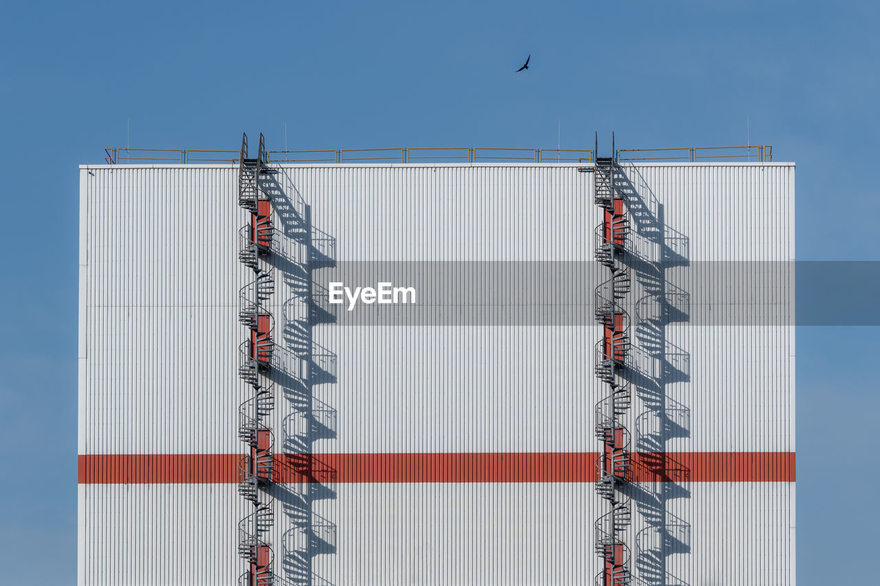 Low angle view of birds on building with spiral stairs outside against sky
