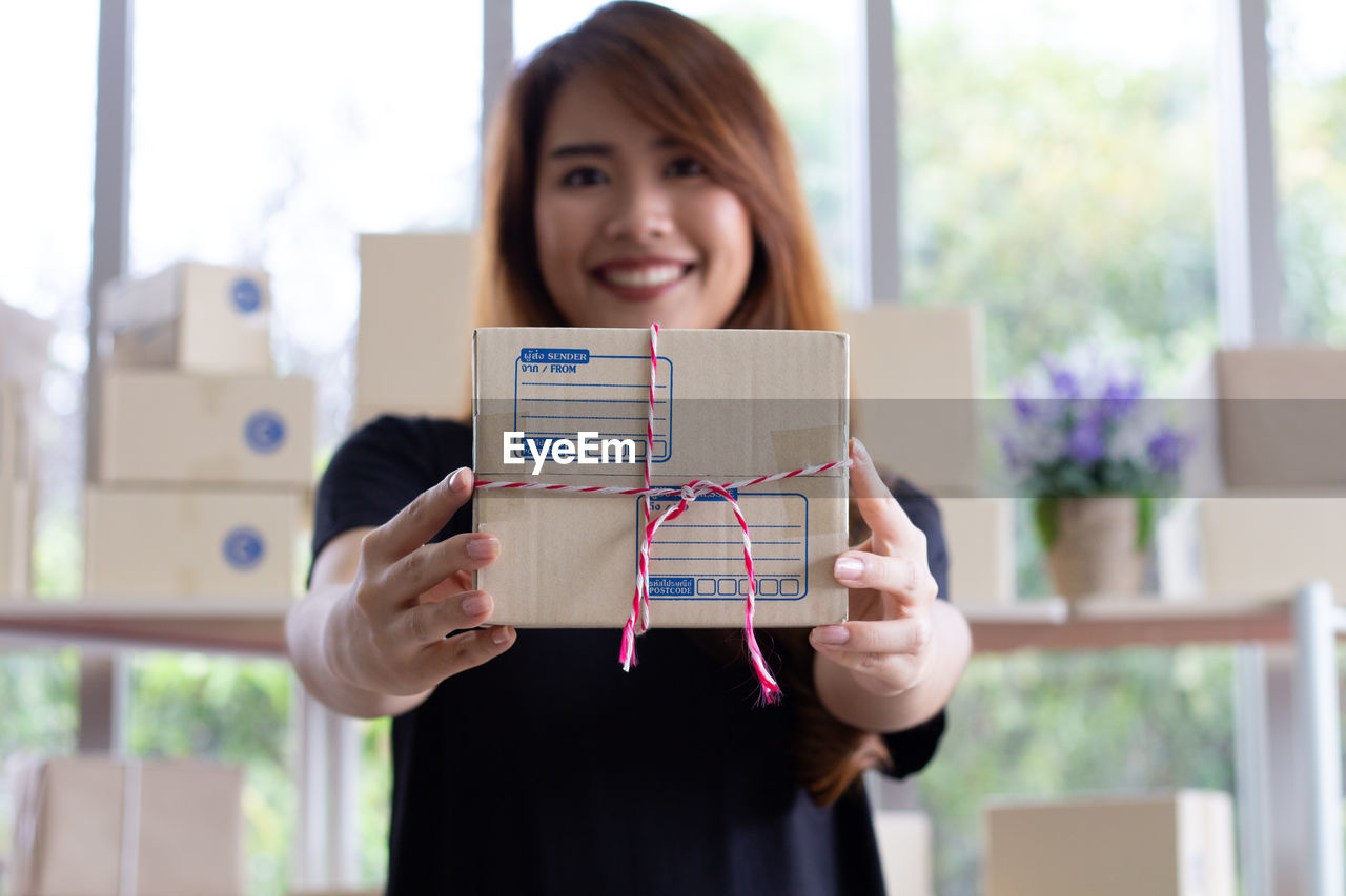 Portrait of smiling woman holding box