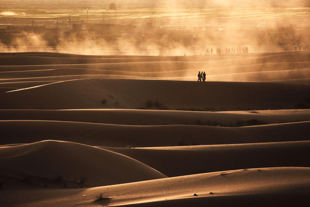 People on desert during sunset