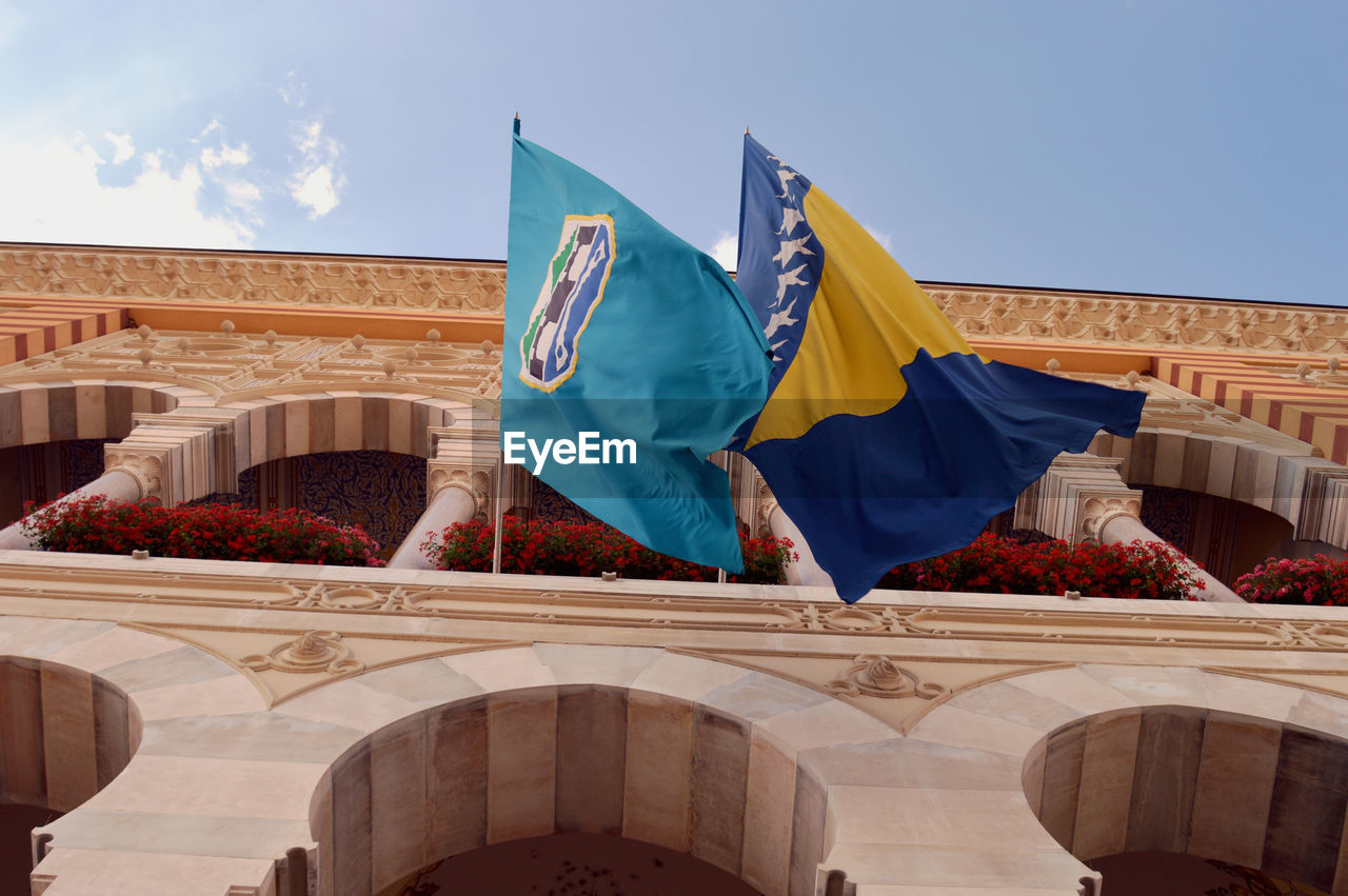 Low angle view of bosnia herzegovinan flag and coat of arms flag on historic building