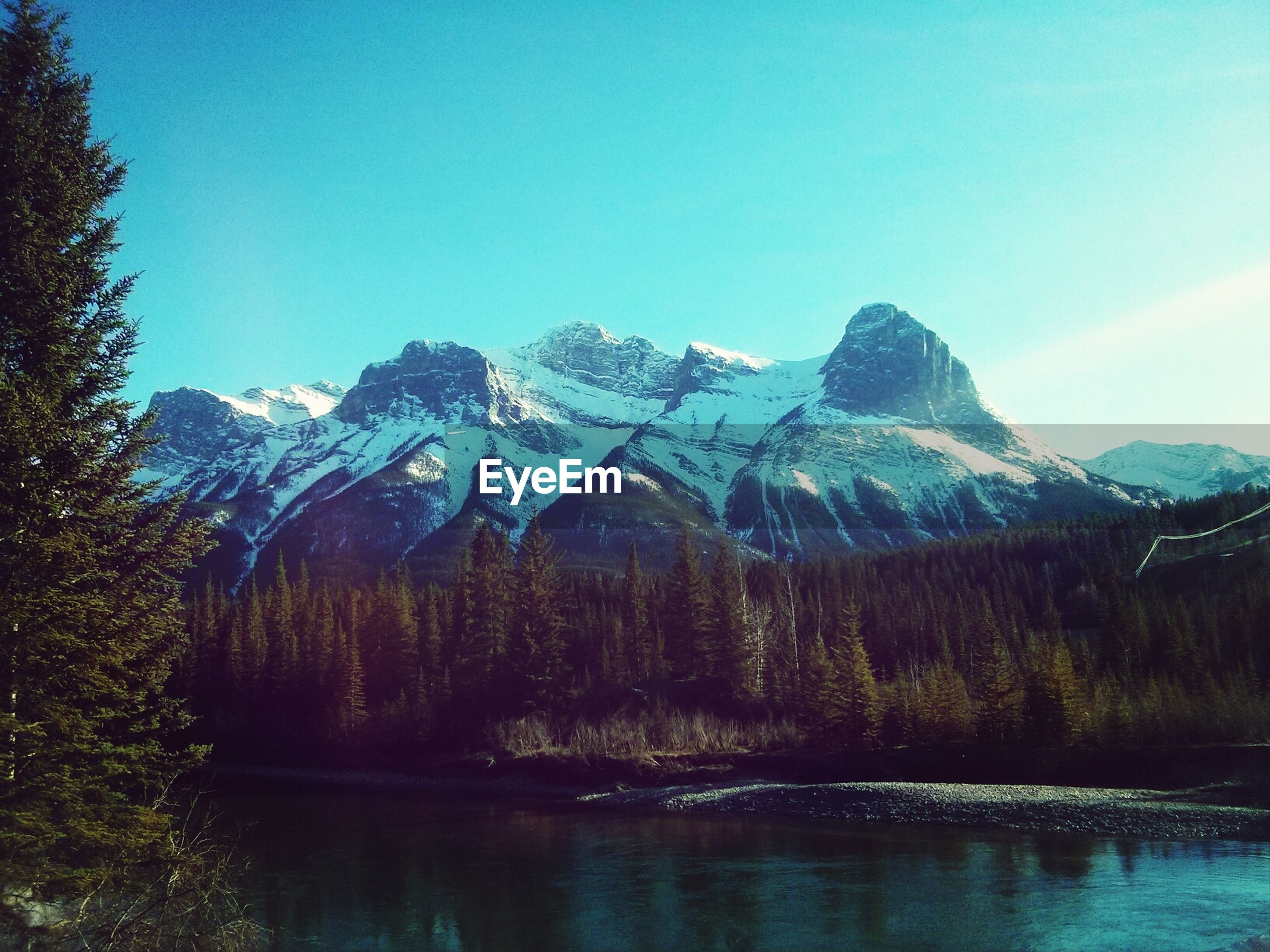mountain, tranquil scene, mountain range, water, tranquility, clear sky, scenics, lake, beauty in nature, waterfront, tree, nature, blue, snow, winter, reflection, copy space, idyllic, cold temperature, non-urban scene