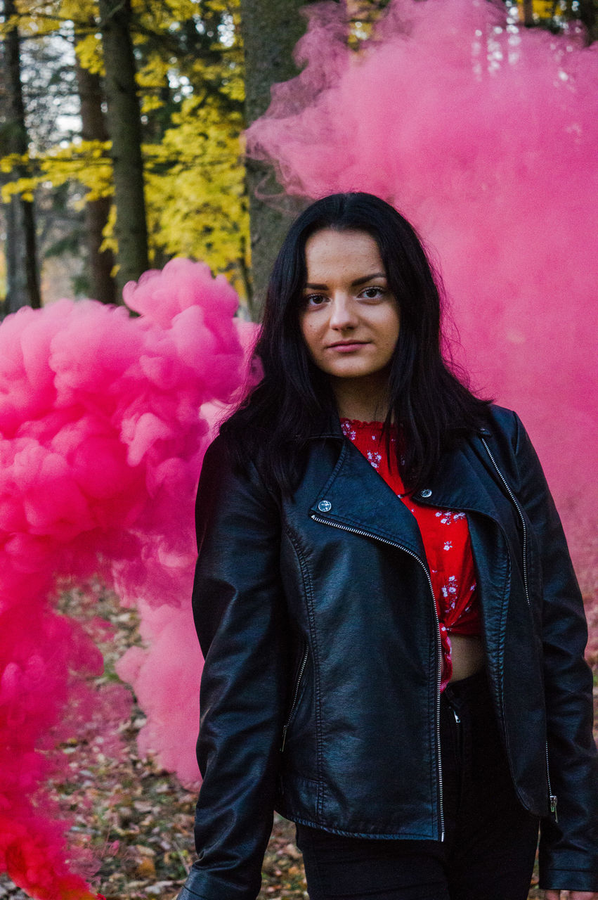 Portrait of smiling woman standing around pink smoke in forest