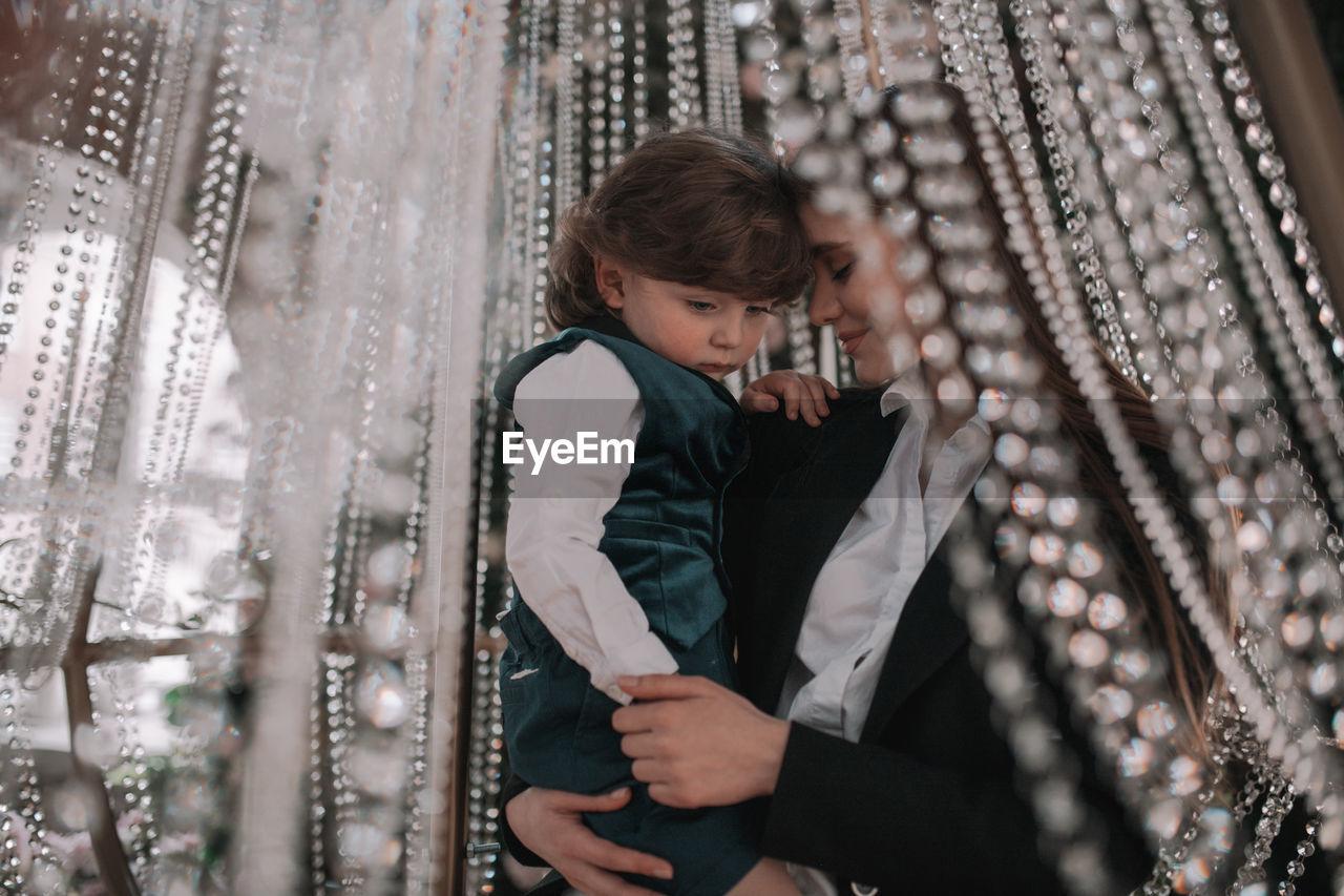 Woman holding boy under illuminated decoration