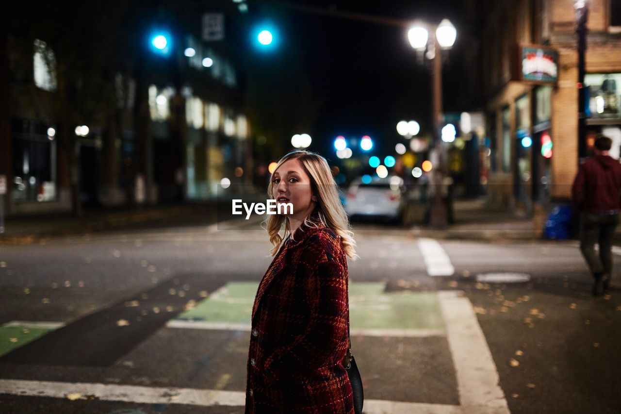 Portrait Of Young Woman On Street At Night