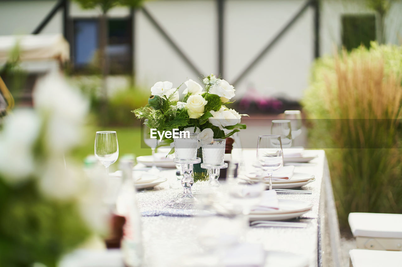 WHITE FLOWERS IN VASE ON TABLE AT DINING