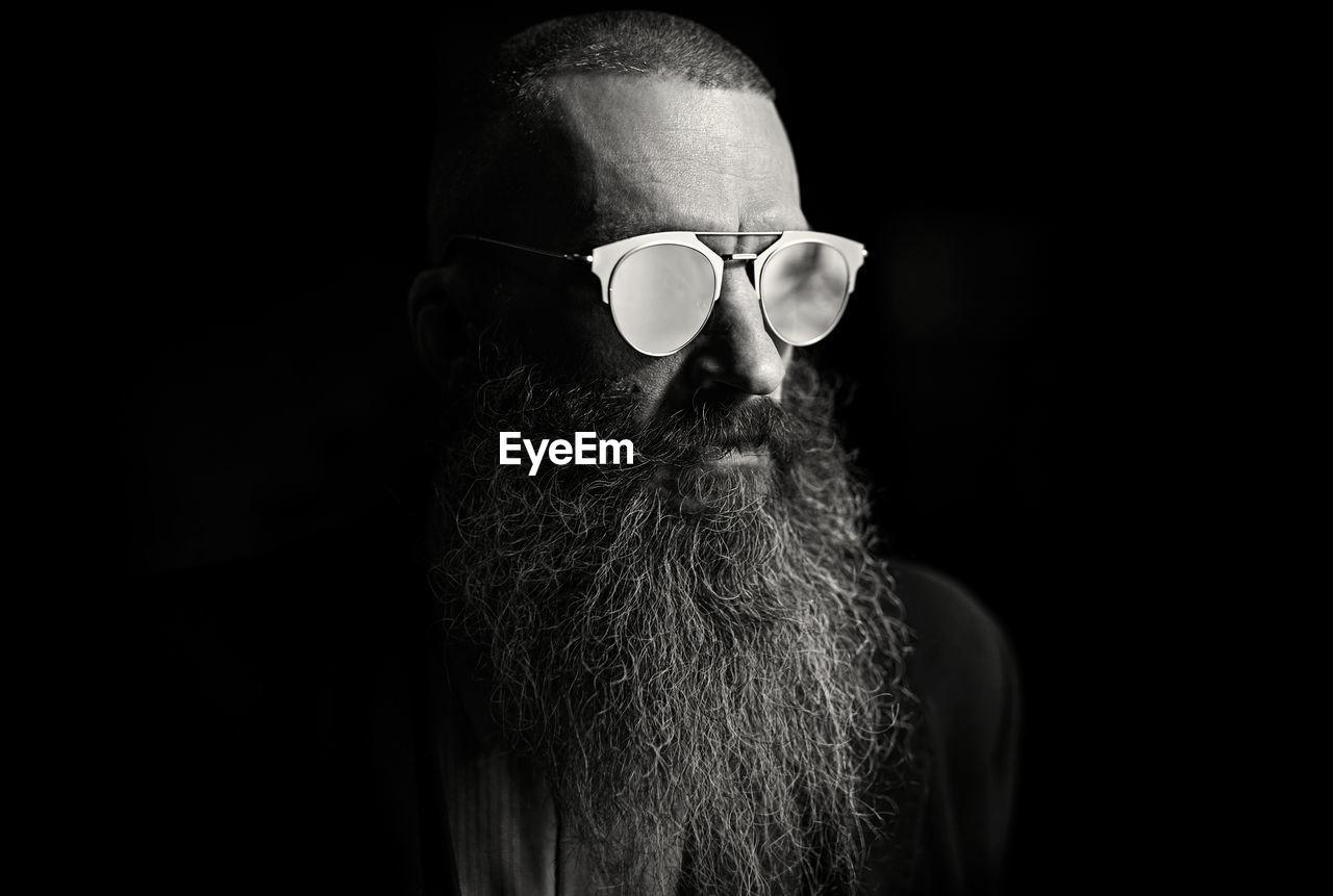 Bearded man wearing sunglasses against black background