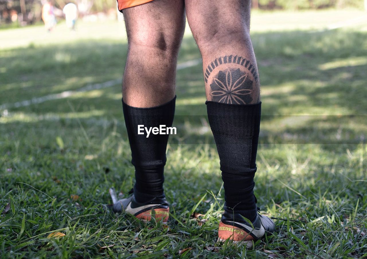 human leg, grass, one person, human body part, body part, low section, day, plant, nature, land, real people, standing, focus on foreground, shoe, field, lifestyles, men, limb, outdoors, human limb, jeans, human foot, shorts