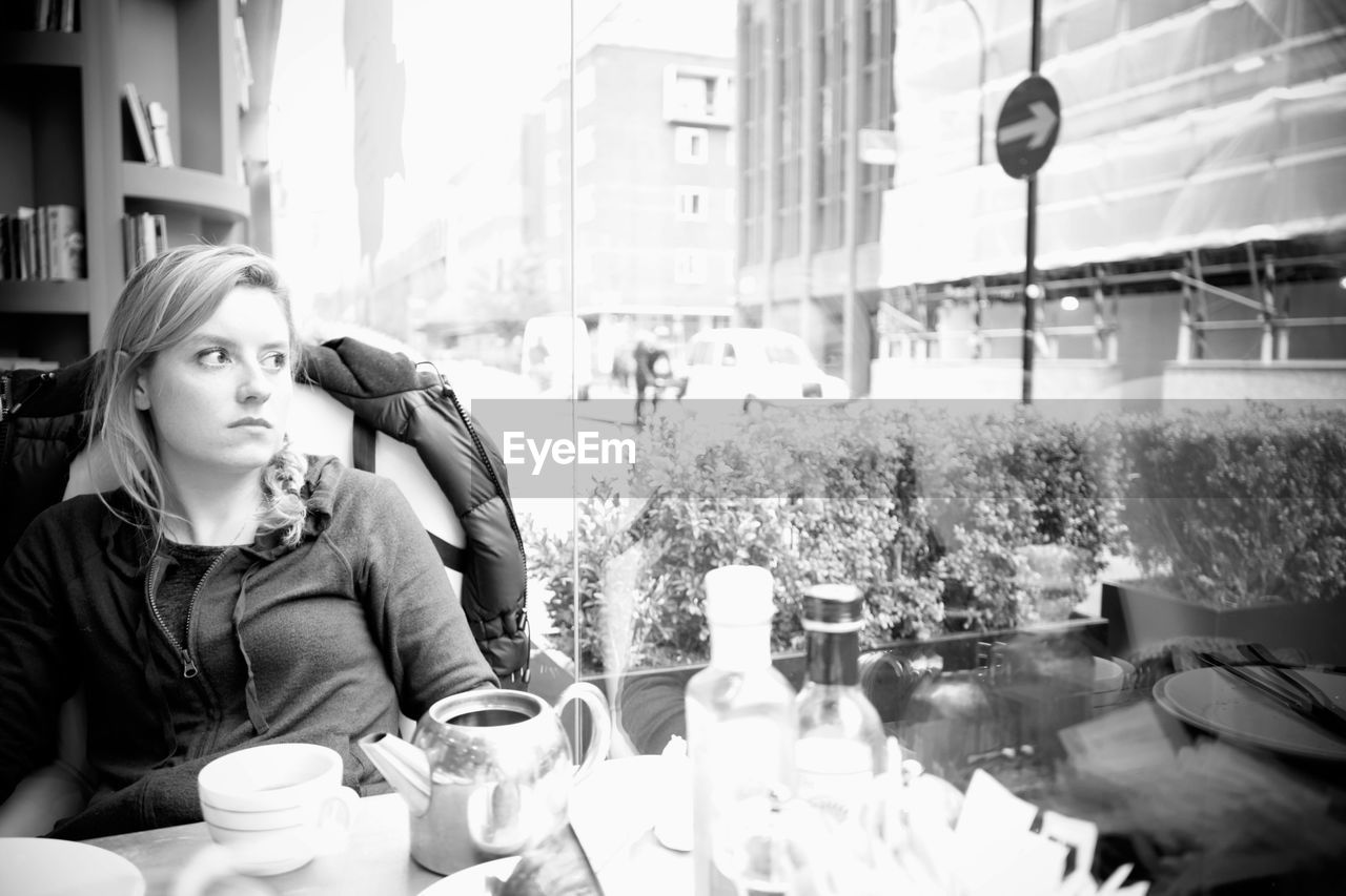 real people, one person, coffee cup, building exterior, food and drink, coffee - drink, architecture, built structure, outdoors, store, leisure activity, retail, day, drink, lifestyles, sitting, young women, city, young adult, people