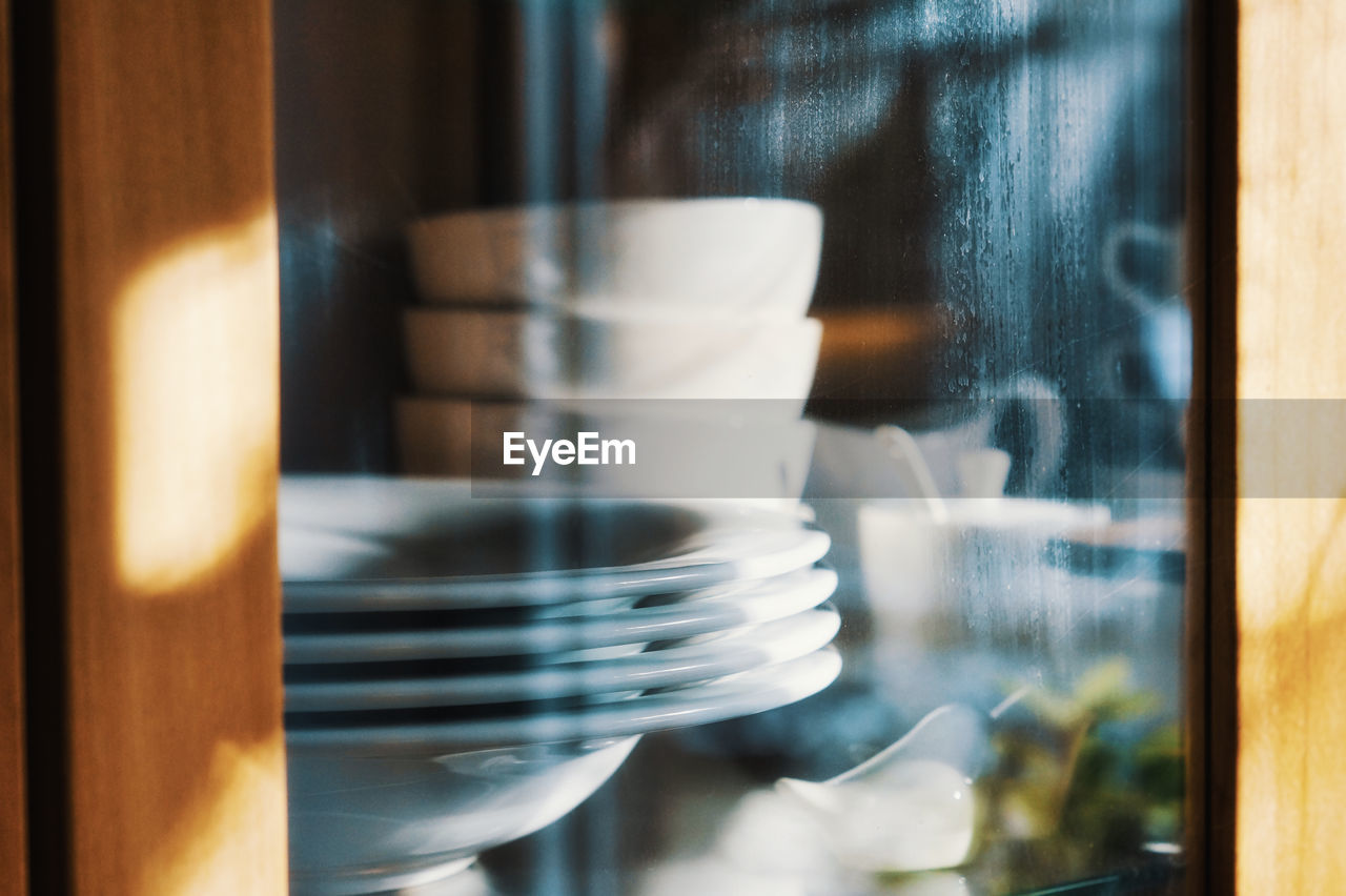 window, indoors, food and drink, no people, transparent, close-up, glass - material, selective focus, still life, focus on foreground, day, reflection, kitchen utensil, business, crockery, restaurant, cafe, wood - material, glass, household equipment