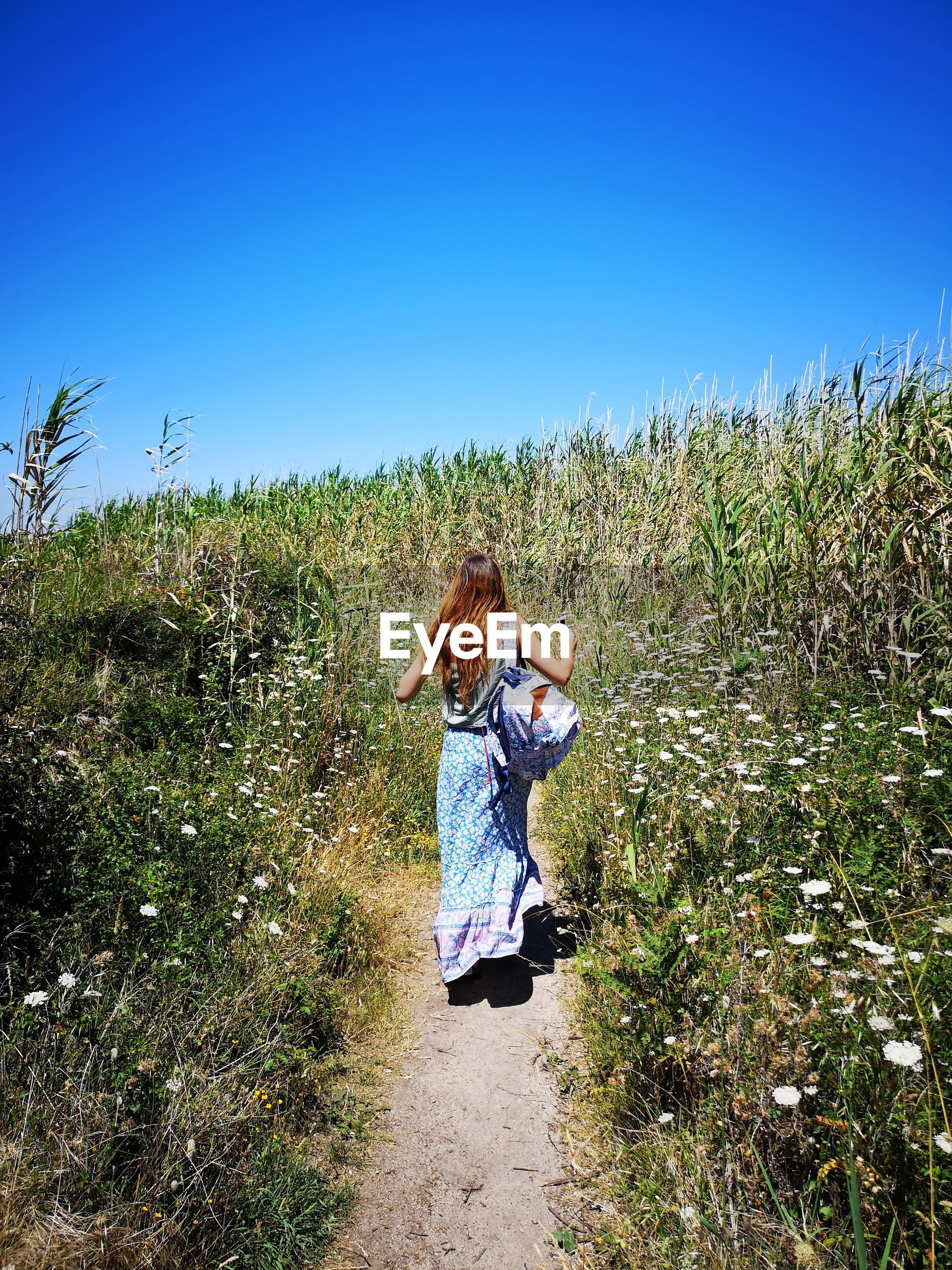 Woman walking on land against clear blue sky