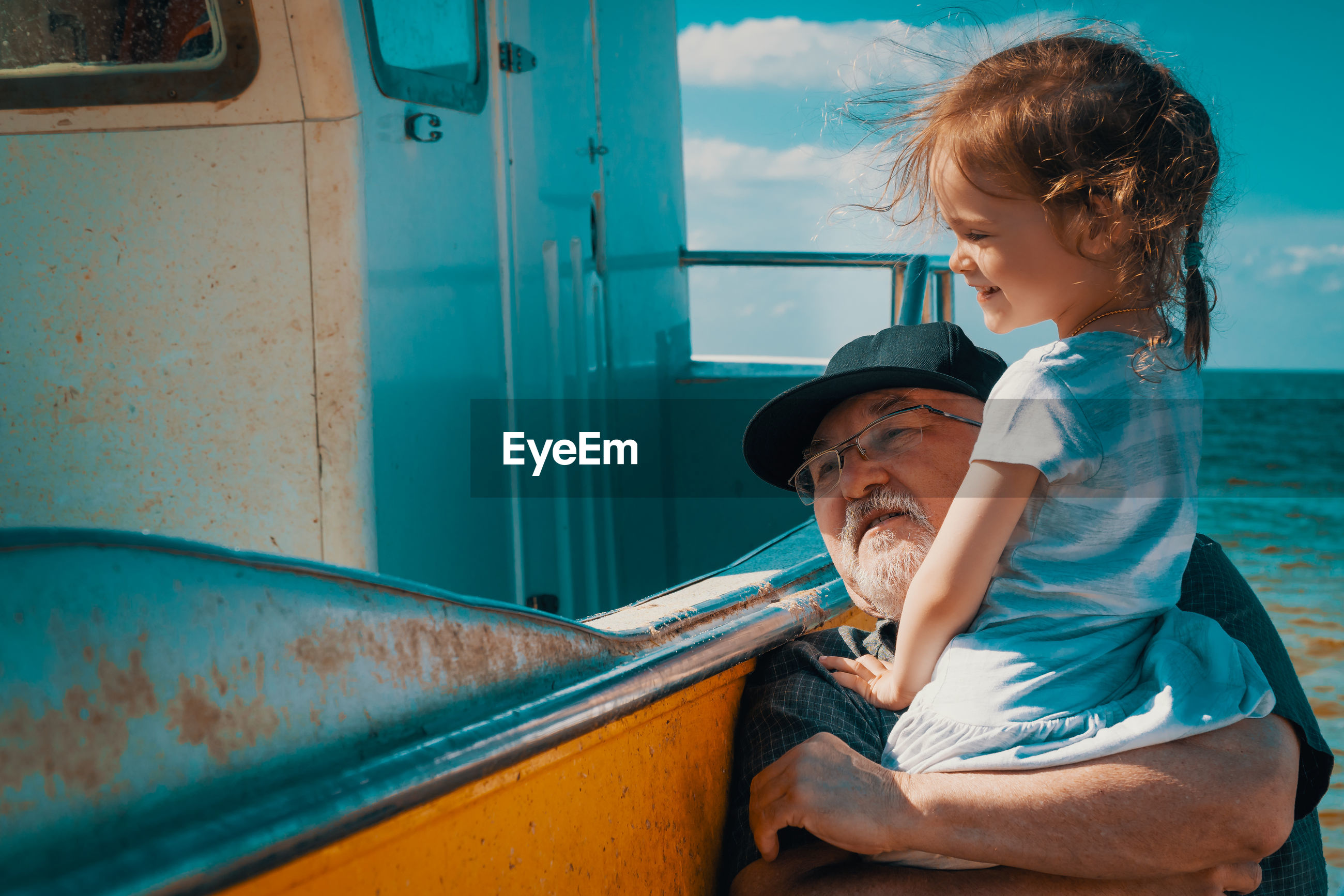 Grandfather and granddaughter by boat at beach
