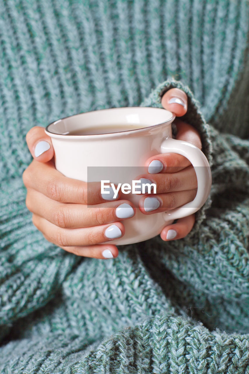 human hand, drink, cup, one person, hand, refreshment, holding, mug, human body part, food and drink, real people, coffee, adult, coffee cup, hot drink, midsection, women, close-up, coffee - drink, tea, tea - hot drink, finger, warm clothing, drinking, nail, tea cup