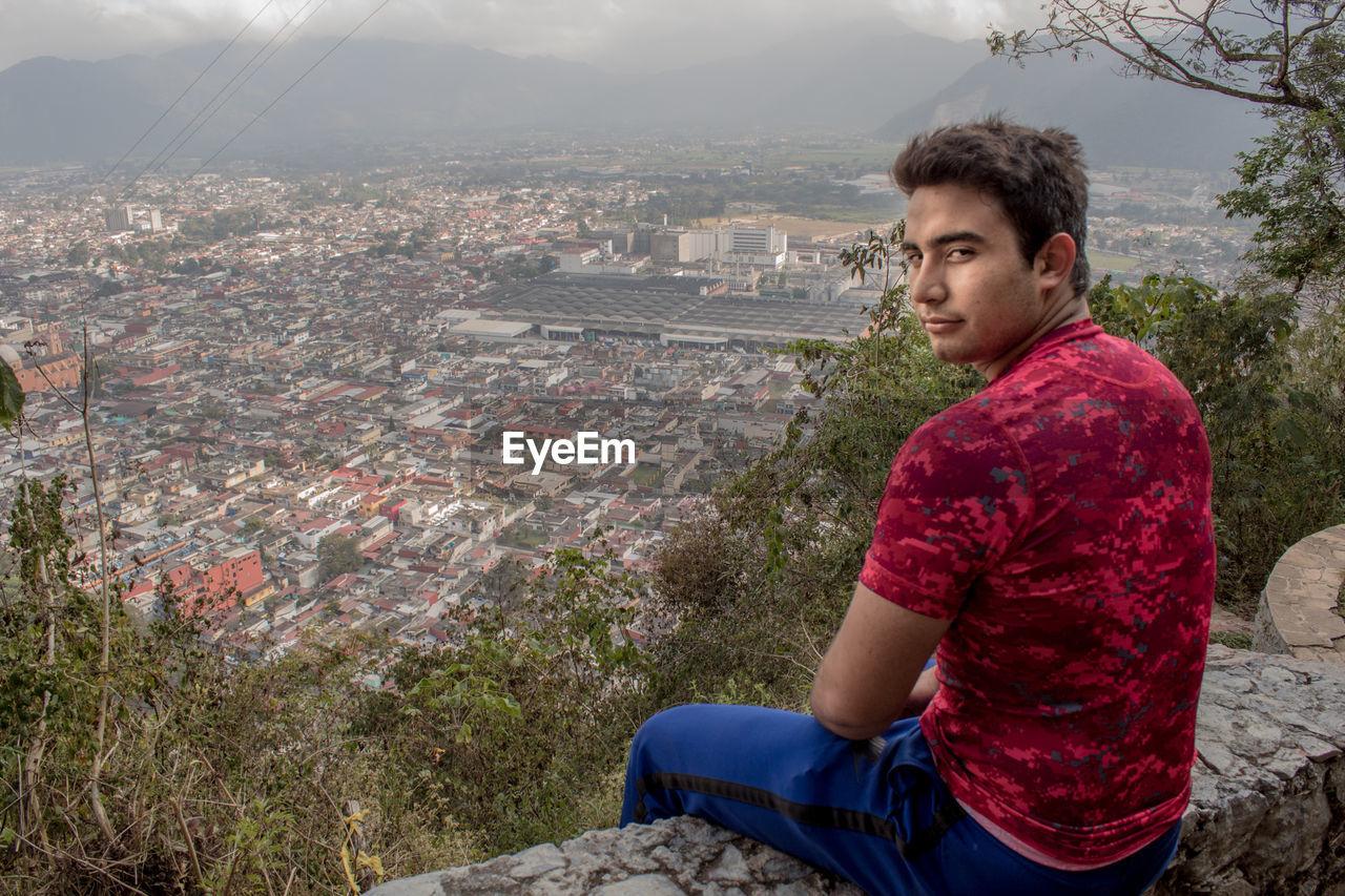 Portrait of teenage boy sitting on retaining wall against cityscape