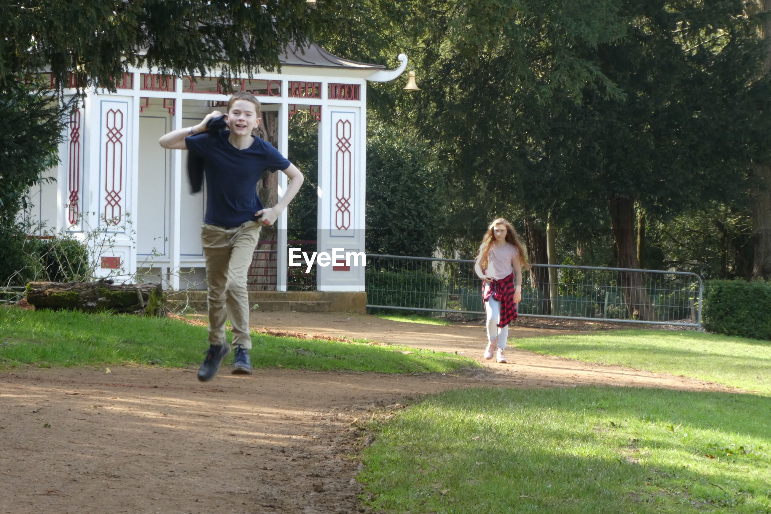 Full length of boy running while sister walking in background at park