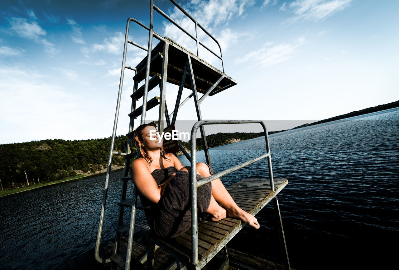 Woman Relaxing By Diving Platform By Lake