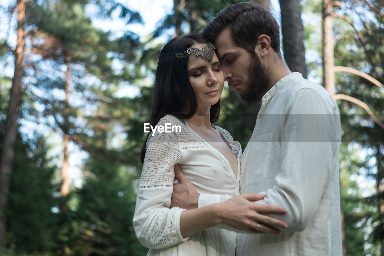 Romantic couple embracing while standing in forest