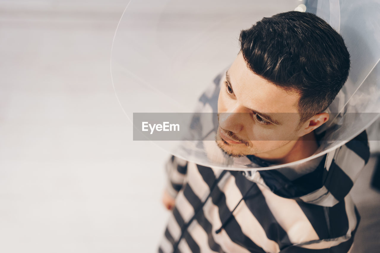 High Angle View Of Man Wearing Protective Collar By Wall