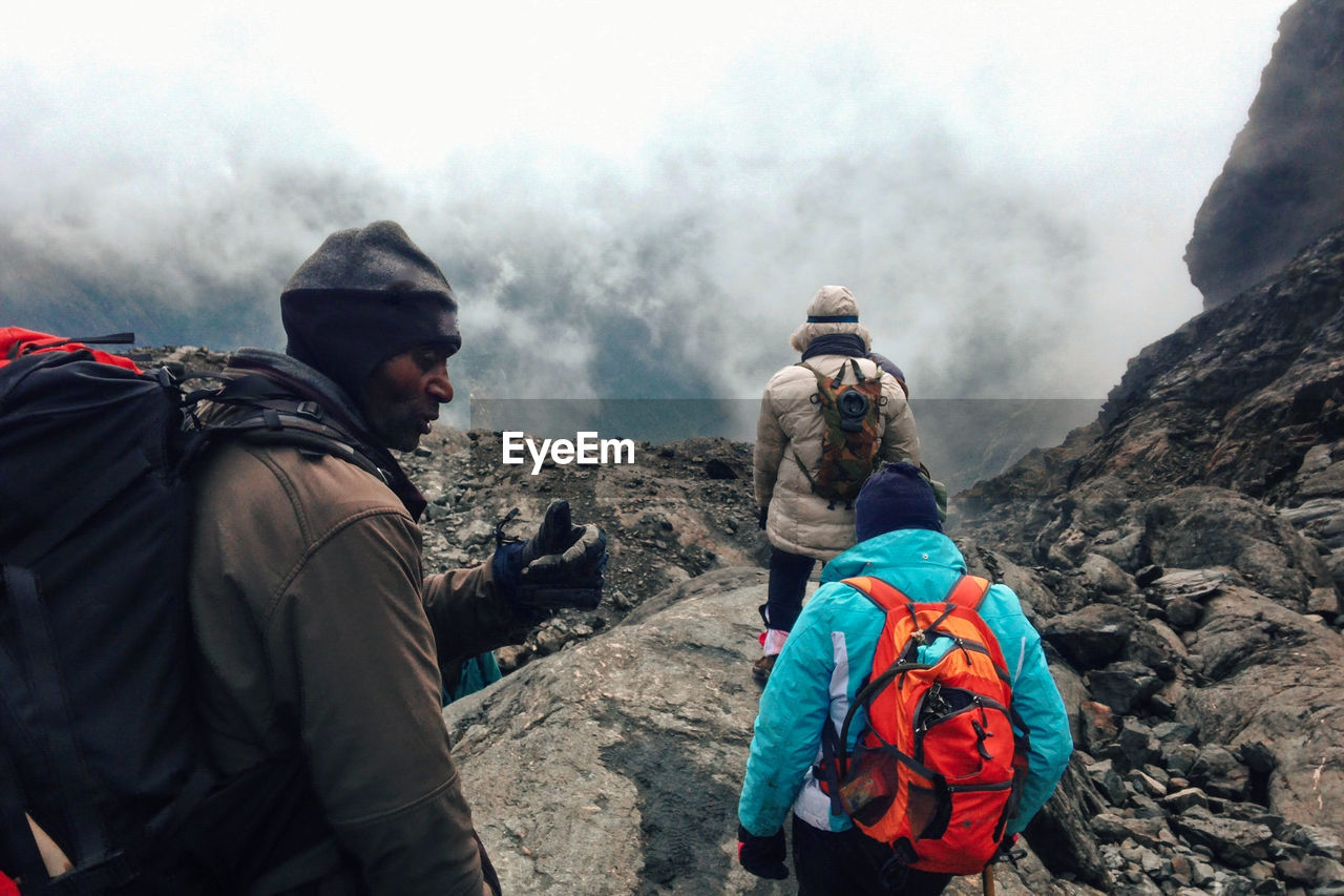 A group of hikers in the panoramic mountain landscapes of rwenzori mountains, uganda