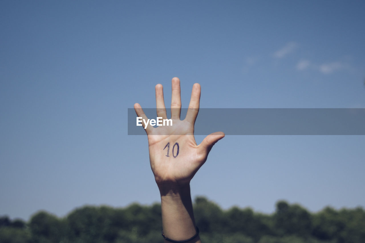 Cropped Hand Of Person With Numbers On Palm Against Sky
