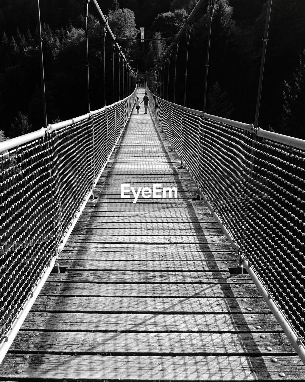 Rear view of boys walking on footbridge