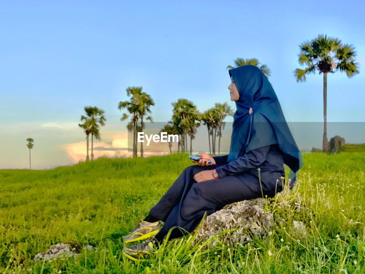 Side view of woman sitting on rock with mobile phone amidst grass against blue sky