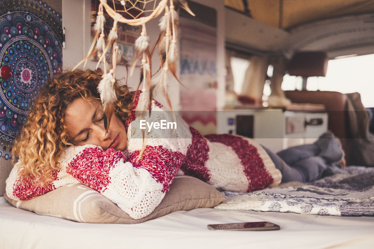 Young Woman Sleeping On Bed In Caravan