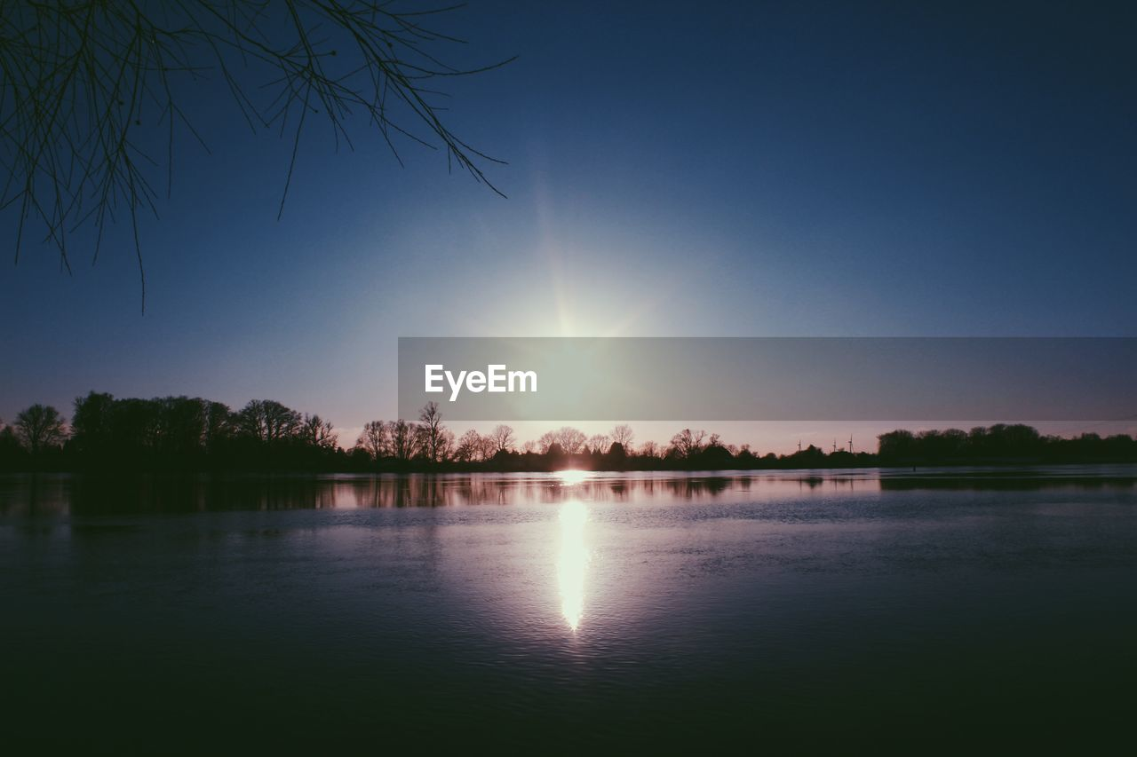 reflection, sun, scenics, tranquil scene, beauty in nature, nature, tranquility, water, sunset, tree, no people, lake, idyllic, outdoors, sunlight, sky, clear sky, day