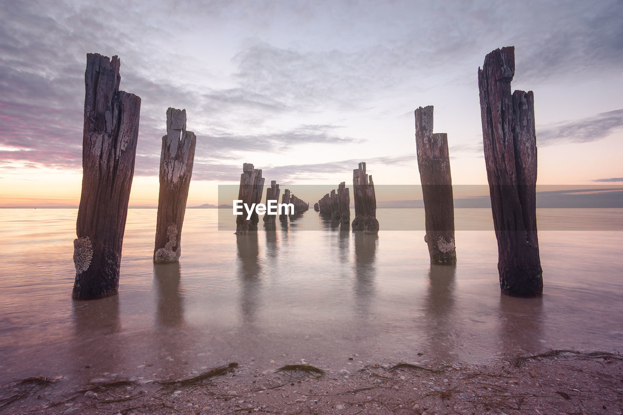 Wooden Posts On Beach Against Cloudy Sky During Sunset