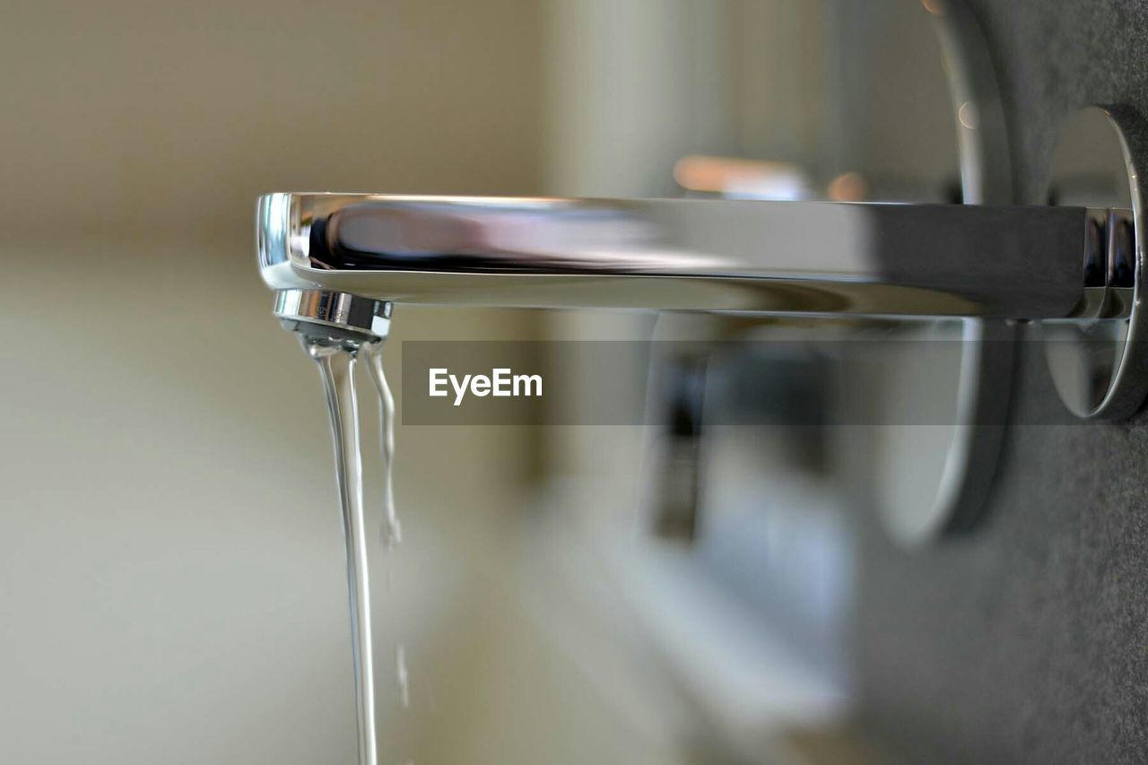 Close-up of water running from faucet in bathroom